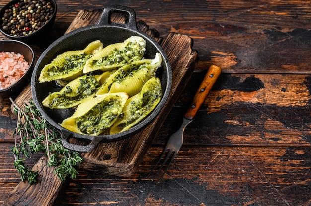 Jumbo muszle włoski makaron conchiglioni konkiloni nadziewany mięsem wołowym i szpinakiem na drewnianym stole. widok z góry.