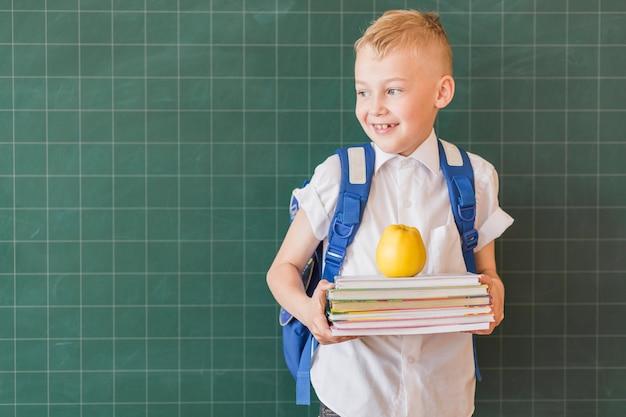 Junior z plecakiem i podręcznikami w pobliżu tablicy