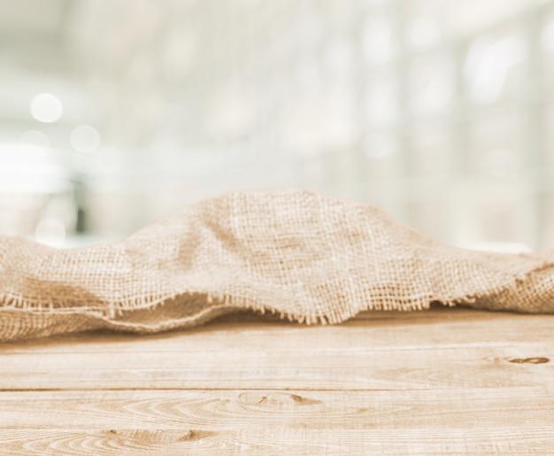 Juta tekstura na drewnianym stole na zamazanym tle