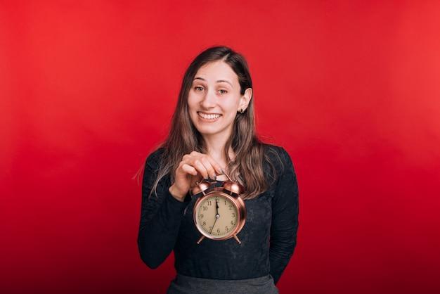 Już czas. rozochocona kobieta trzyma budzika i ono uśmiecha się przy kamerą na czerwieni przestrzeni.