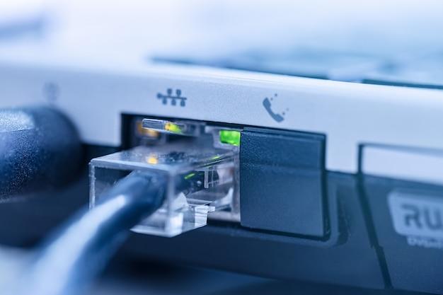 Kabel sieci lan podłączony do notebooka z portem rj-45 z bliska