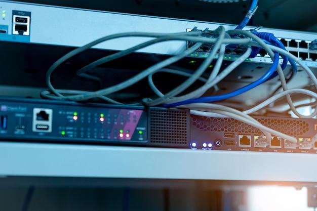 Kable ethernet i przełącznik sieciowy w centrum danych. wtyczka wi-fi routera internetowego do komputera. hub sieciowy. sprzęt checkpoint dla bezpieczeństwa danych. sieć internetowa.