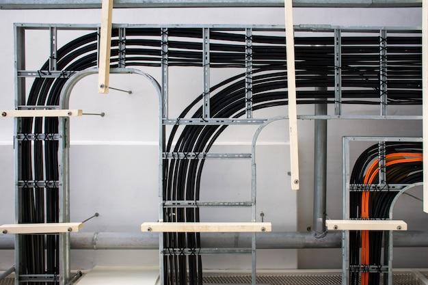 Kable zasilania elektrycznego i kable oprzyrządowania na tacy w sterowni elektrycznej.