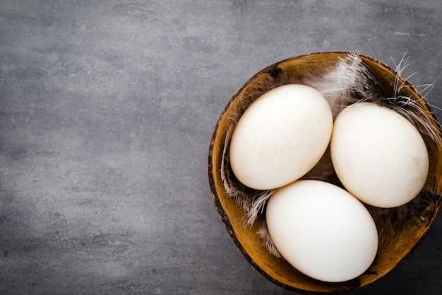 Kacze jaja na szarym tle klatki.