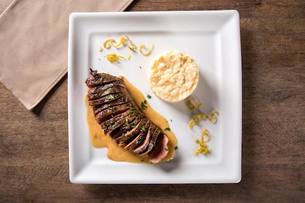 Kaczka magret z sosem tucupi i risotto jambu.
