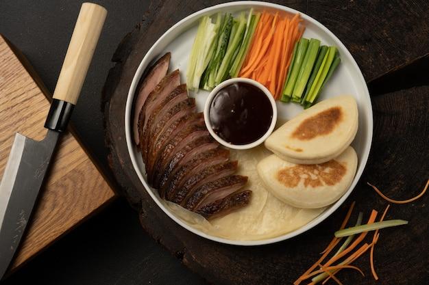 Kaczka po pekińsku ze świeżą bułką bao. tradycyjne chińskie danie z filetu drobiowo-warzywnego z sosem teriyaki
