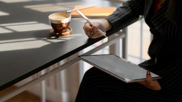 Kadrowanie przedsiębiorców piszących na cyfrowym tablecie w wygodnym miejscu do pracy