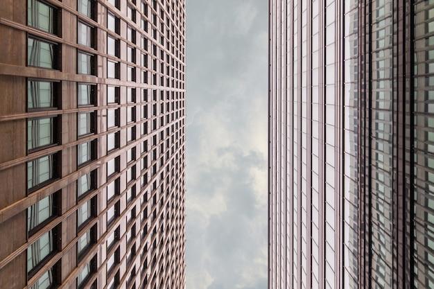 Kadrowanie z fasady budynku biurowego strzał z dna up z pionowym paskiem szarego nieba z chmurami. centrum biznesowe w pochmurny dzień