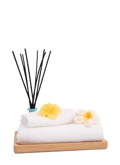 Kadzidełka, kwiat plumaria, świeca i białe ręczniki w spa lub wannie na białym tle na białym tle ze ścieżką przycinającą, aromaterapia spa wellness