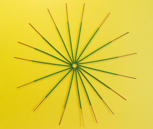 Kadzidełka ułożone w okrąg na żółtym tle