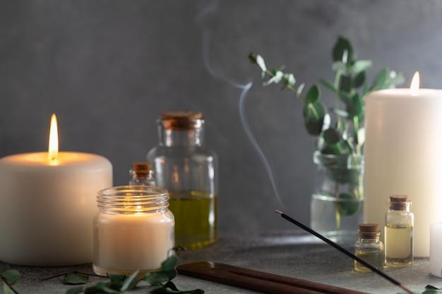 Kadzidełka z dymem na kamieniu z białymi świecami i olejkami eterycznymi