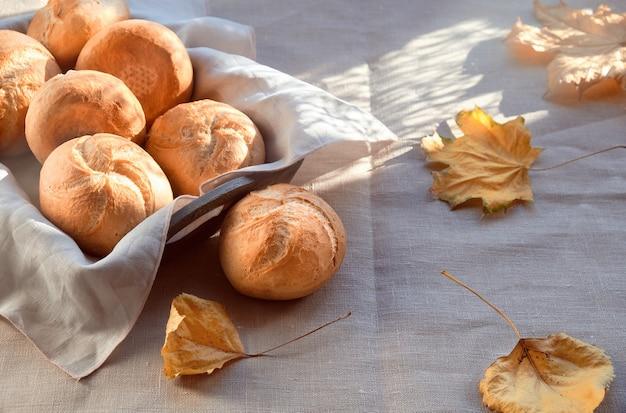 Kaiser lub wiedeńskie bułeczki w koszyku chleba na tle włókienniczych z żółtymi liśćmi jesieni.