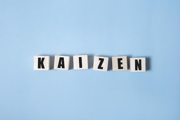 Kaizen - słowa z drewnianych klocków z literami, japońska filozofia biznesu kaizen, białe tło.