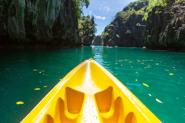 Kajak w lagunie wyspy między górami. spływ kajakowy w el nido, palawan, filipiny.