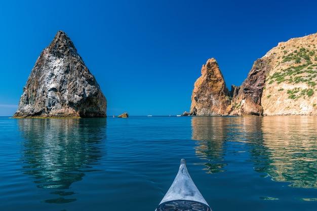 Kajak w spokojnym, czystym, błękitnym morzu, skalny orest i pilad, przylądek fiolent w balaklavie, sewastopol na krymie. koncepcja aktywnego i zdrowego życia w zgodzie z naturą.