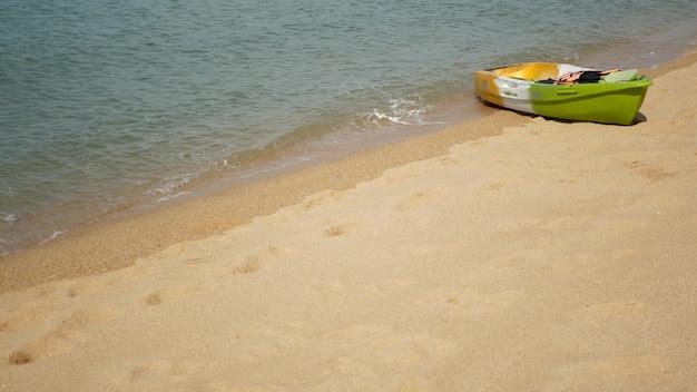 Kajak z wiosłami na piaszczystym brzegu obmywanym przez fale błękitnego morza
