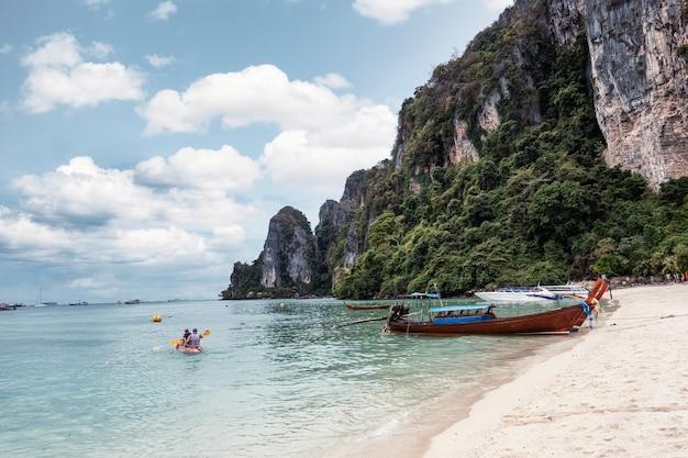 Kajakarstwo turystyczne z drewnianą łodzią i góry na wybrzeżu w tropikalnym morzu na wyspie phi phi, krabi