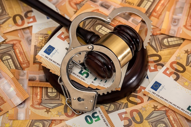 Kajdanki i banknoty euro. koncepcja korupcji i łapówkarstwa