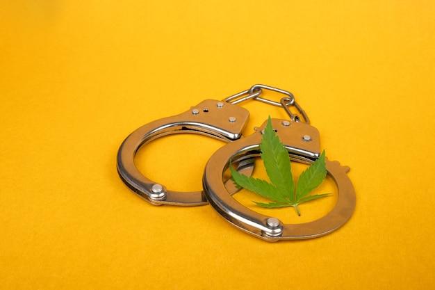Kajdanki i liść konopi na żółtym tle, areszt za nielegalną dystrybucję marihuany.
