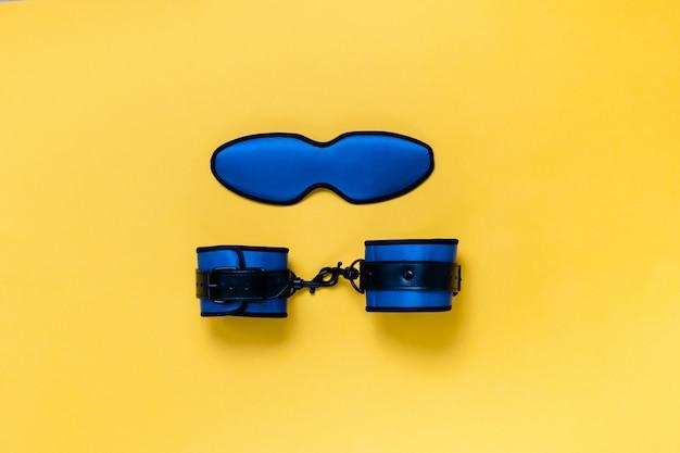 Kajdanki i maska do spania na żółtym tle