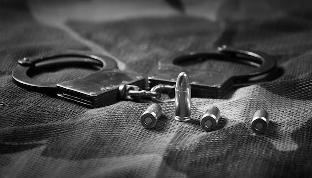 Kajdanki i naboje leżą na tle kamuflażu. pojęcie trybunału wojskowego, naruszenie prawa, przestępstwo. widok z góry. różne środki przekazu