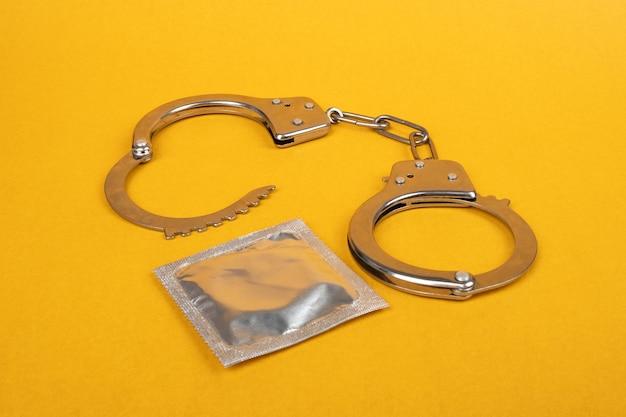 Kajdanki i prezerwatywy na żółtym tle, nielegalna prostytucja seksualna.