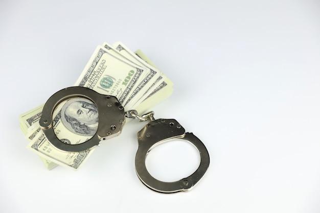 Kajdanki metalowe na stosy banknotów 100 dolarów na białym tle
