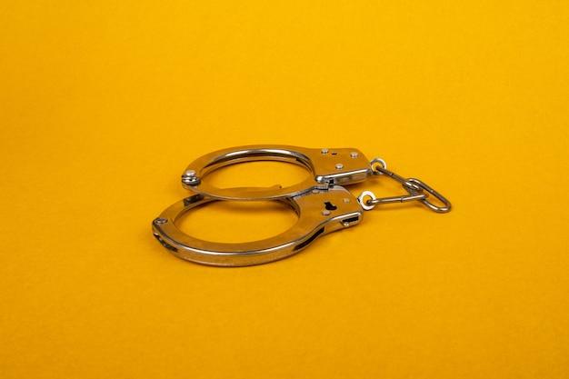 Kajdanki na żółtym tle, pojęcie aresztowania.