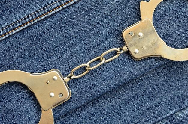 Kajdanki policji ze stali leżące na tle ciemnych niebieskich dżinsów