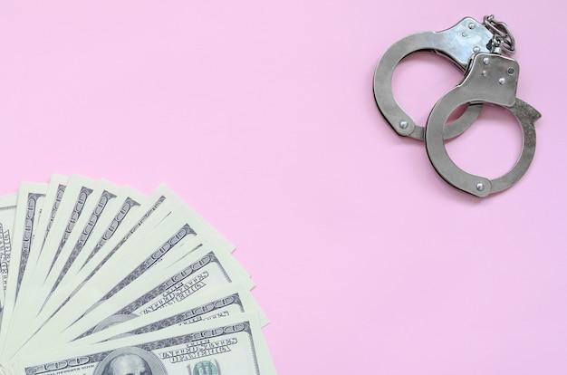 Kajdanki policyjne i setki dolarów leżą na różowym tle