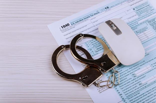 Kajdanki policyjne leżą na formularzu podatkowym 1040