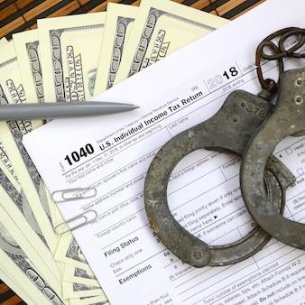 Kajdanki policyjne leżą na formularzu podatkowym 1040.