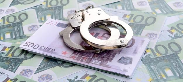 Kajdanki policyjne leżą na zestawie zielonych nominałów pieniężnych w wysokości 100 euro.