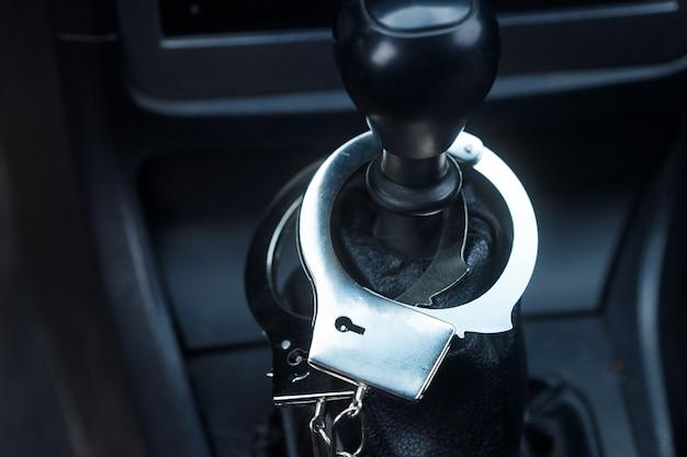 Kajdanki wiszą w samochodzie na gałce zmiany biegów. przestępstwa drogowe. zdjęcie wysokiej jakości