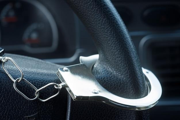 Kajdanki wiszące na kierownicy samochodu. zdjęcie wysokiej jakości