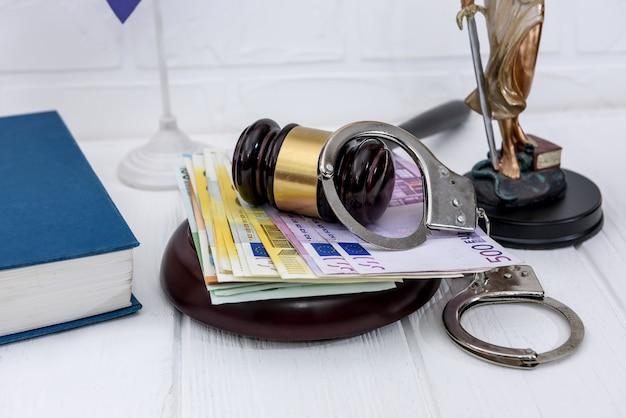 Kajdanki z banknotami euro i młotkiem sędziego