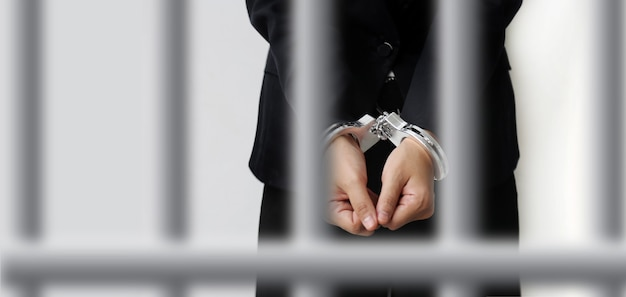 Kajdanki zamykają kajdany oskarżonego, aby uwięzić postępowanie wyjaśniające po sądzie. na białym tle z klatka rozmycie