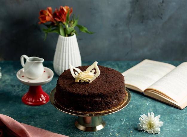 Kakao kruszy ciasto ozdobione białymi liśćmi czekolady i śmietaną
