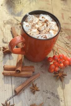 Kakao lub filiżanka kawy ze smacznymi piankami, gałązką jodły, jagodami czerwonej jarzębiny