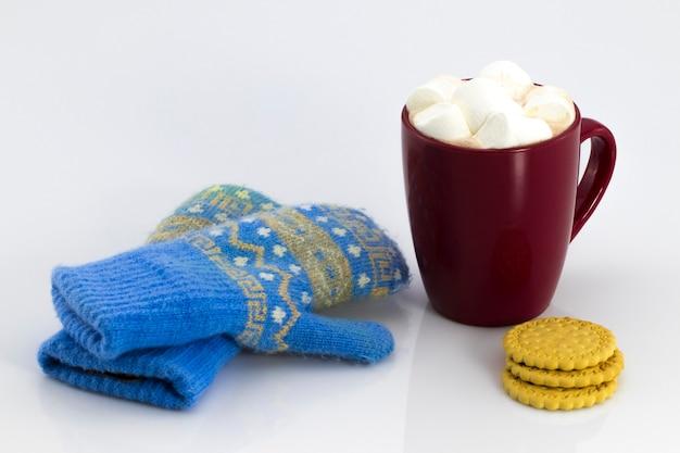 Kakao w czerwonym kubku z piankami i herbatnikami, izolowana na białym tle