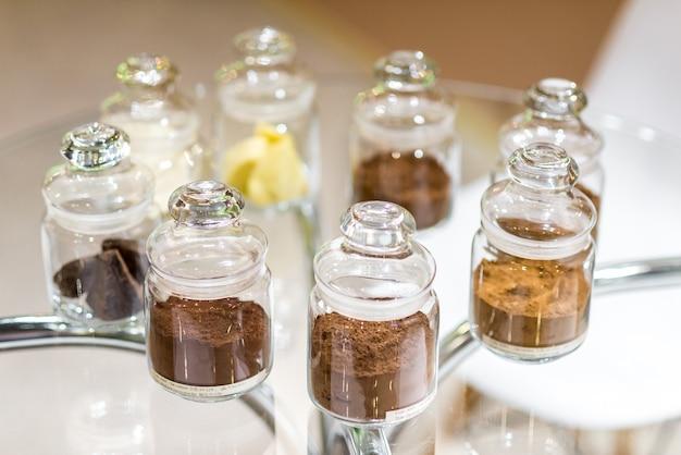 Kakao w proszku zwykłe i alkalizowane z czekoladą deserową, w szklanych słojach z pokrywkami.