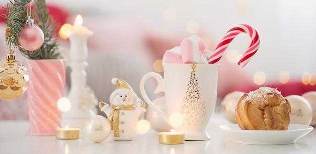 Kakao z pianką i świątecznym wystrojem w różowo-złotej kolorystyce