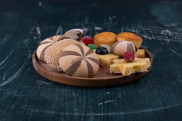 Kakaowe ciasteczka i bułeczki z jagodami na drewnianym talerzu
