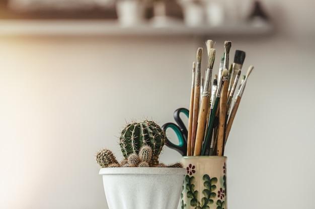 Kaktus w białej doniczce i zestaw pędzli do malowania.