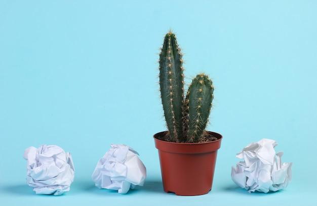 Kaktus w doniczce i zmięte papierowe kulki na niebieskim studio