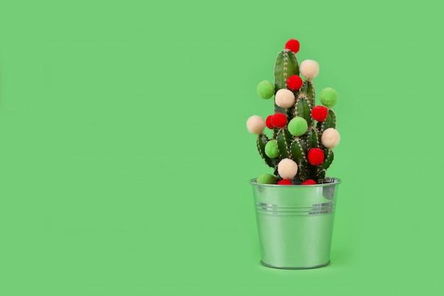 Kaktusowe drzewo w doniczce, ozdobione kolorowymi kulkami
