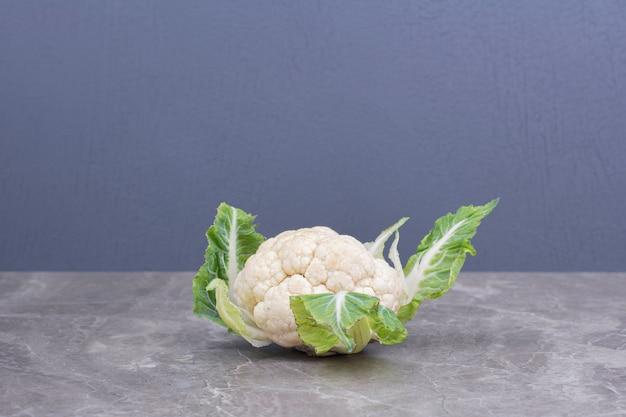 Kalafior biały z zielonymi liśćmi na marmurze