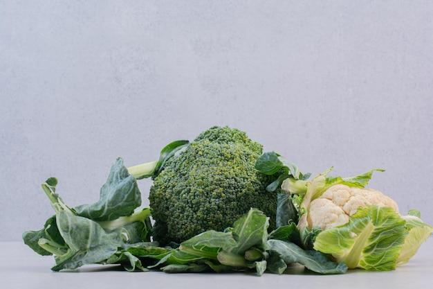 Kalafior i brokuły na białym stole.