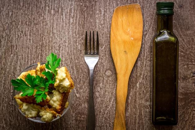 Kalafior pieczony w cieście na talerzu na drewnianym tle. widok z góry. skopiuj miejsce. martwa natura. płaskie ułożenie
