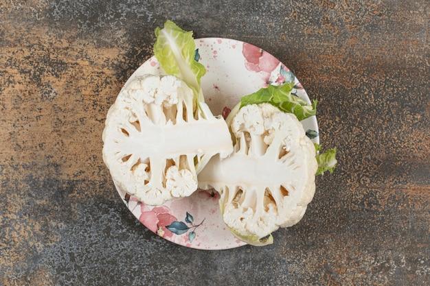 Kalafior podzielony na pół na talerzu, na marmurowej powierzchni
